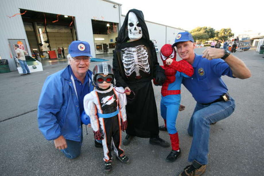 Harris County Precinct 3 employees Lou Hickman, eft,and Mark Wilburn pose with Dustin Gartman, 4, as a Power Ranger,  Dylon Greenwood, 10, as a skeleton and Devin Gartman, 6, as Spiderman at Commissioner Steve Radack's Safe Halloween Night. Photo: Suzanne Rehak, For The Chronicle