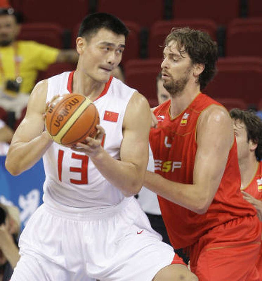China's center Yao Ming, left, works the ball against Spain's Pau Gasol, right, during the first quarter of their men's preliminary game at the Beijing 2008 Olympics in Beijing on Tuesday Photo: Eric Gay, AP