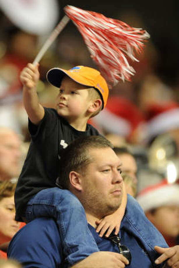 Maxumus Richardson, 4, cheers on the Katy Tigers while sitting on the shoulders of his father, James Richardson. Photo: Ronnie Montgomery, For The Chronicle