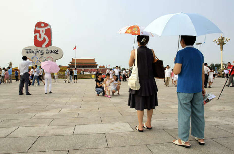 July 29, 2008: Good day for sunshine. Tourists even had to bring out umbrellas at Tiananmen Square after a storm blew out a lot of the smog. Photo: Robert F. Bukaty, AP