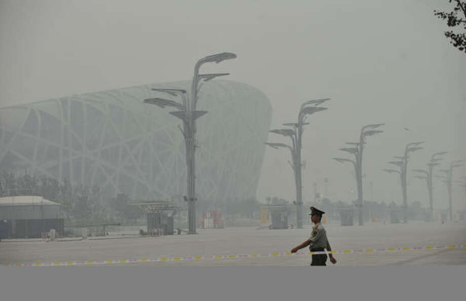 July 27, 2008:A paramilitary policeman marches past the National Stadium, seen through thick smog. Photo: PETER PARKS, AFP/Getty Images