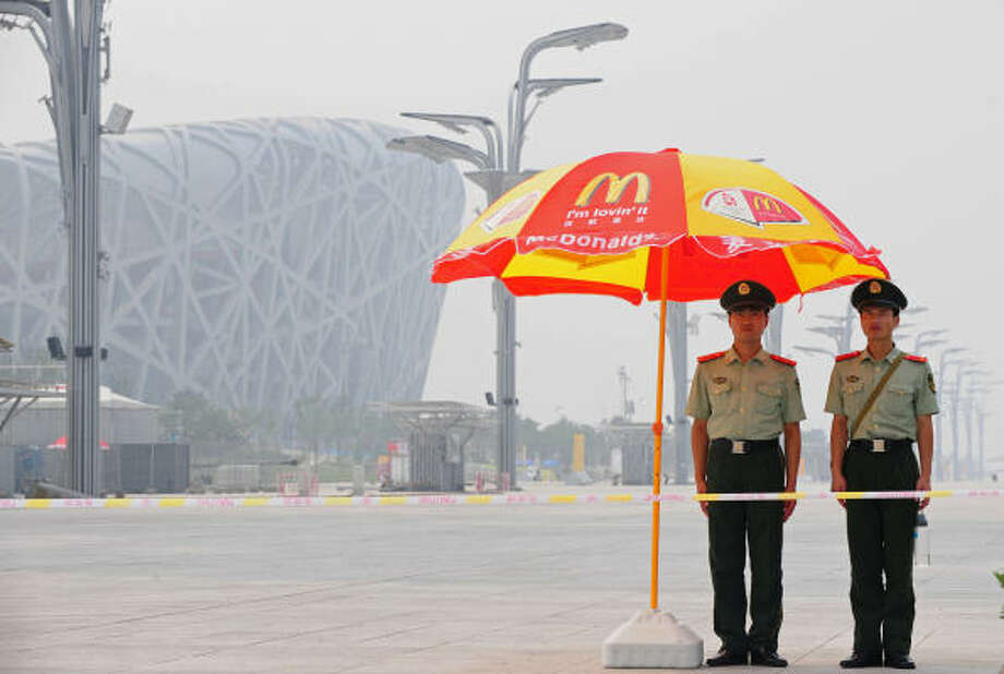 "July 26, 2008:Chinese paramilitary police man their post in a restricted area near the main Olympics stadium, beneath umbrellas sponsored by fastfood giant McDonald's. With less than two weeks to the start of the 2008 Beijing Olympic Games on August 8, the city remains swathed in smog as its notorious pollution defies aggressive steps aimed at clearing the air.  However, Chinese officials who routinely refer to the city's smog as ""fog"", have brushed off concerns over the city's heavy pollution, which has triggered a warning by IOC chief Jacques Rogge that some events could be postponed if air quality is poor. Photo: FREDERIC J. BROWN, AFP/Getty Images"