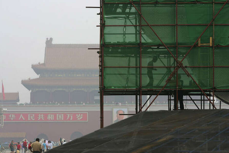 July 24, 2008; Chinese labourers work at an Olympic sculpture on Tiananmen Square shrouded wi