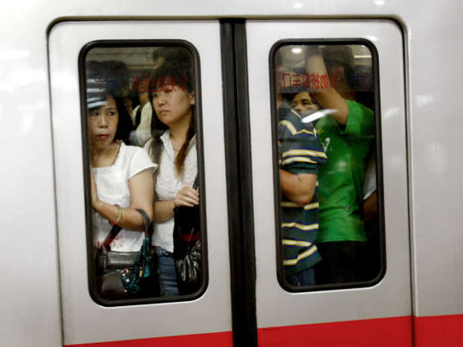 July 21, 2008:Commuters crowd a train at a subway station in Beijing. Many commuters switched to the subway after restrictions on car use went into effect. Photo: Andy Wong, AP