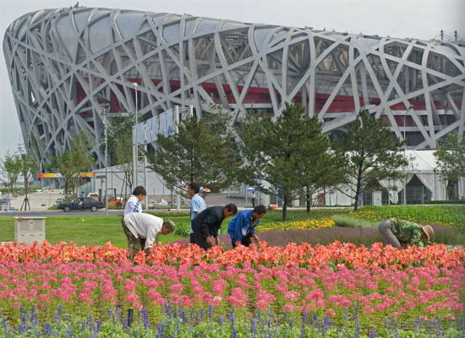 July 15, 2008:Chinese workers plant flowers near the National Stadium, better known as the Bird's Nest, in Beijing. Photo: TEH ENG KOON, AFP/Getty Images
