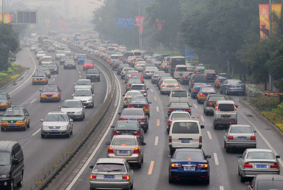 July 14, 2008: Afternoon traffic comes to a standstill on a smog-filled day. Beijing companies have been ordered to reduce working hours from 9:00am to 5:00pm, starting an hour later and finishing an hour earlier than normal, and employers are also encouraged to allow staff to take annual leave during the Games. The start of car ban began on Sunday, July 20. The ban will keep more than one million vehicles off Beijing's roads before and during the Games. Photo: FREDERIC J. BROWN, AFP/Getty Images