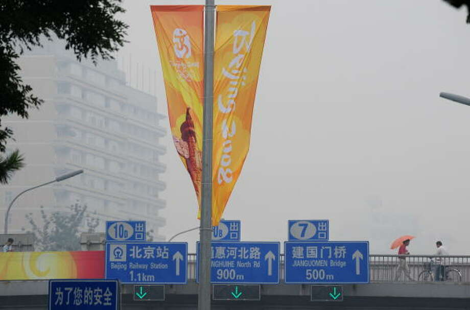 July 14, 2008:Decorative banners for the Olympics brighten up an otherwise smog-filled day in Beijing as pedestrians cross a footbridge, 25 days before the start of the 2008 Beijing Olympic Games. Beijing companies have been told to stagger or shorten working hours beginning next week as the drive to cut pollution and traffic gridlock for the Olympics goes into a high gear. Photo: FREDERIC J. BROWN, AFP/Getty Images