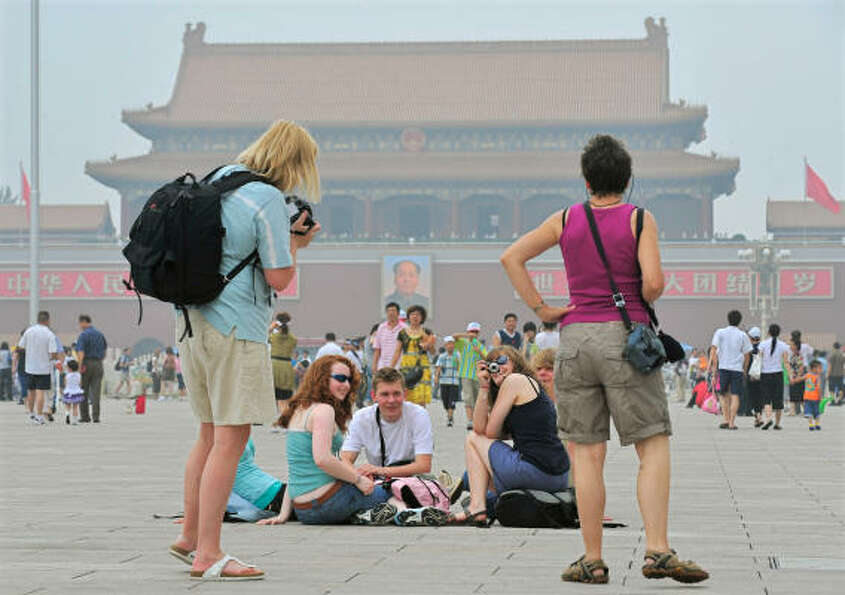 July 10, 2008: Tourists share a laugh with Tiananmen Square shrouded in smog in Beijing. Beij