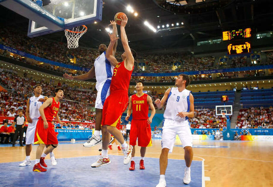 Sofoklis Schortsanitis, center, of Greece leaps to block a shot attempt by Yao Ming during a preliminary round basketball game at the Wukesong Indoor Stadium. Greece won 91-77. Photo: Jamie Squire, Getty Images