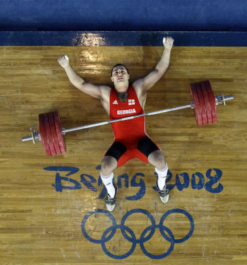 Arsen Kasabiev of Georgia waits for help on the platform after failing an attempt to lift 222 kilograms in the clean and jerk of the men's 94 kg weightlifting competition. Photo: Andres Leighton, AP