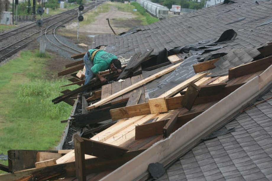 Alex Francisco surveys roof damage at the Cabinet Sales Inc. warehouse done by a possible tornado that hit Houston at approximately 1 p.m. on Friday, Aug. 16, 2008. Photo: Bill Olive, For The Chronicle