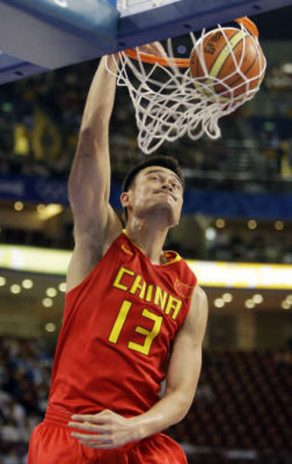 China's Yao Ming dunks against Angola during the first quarter of their men's preliminary basketball game at the Beijing 2008 Olympics on Thursday. Photo: Eric Gay, AP