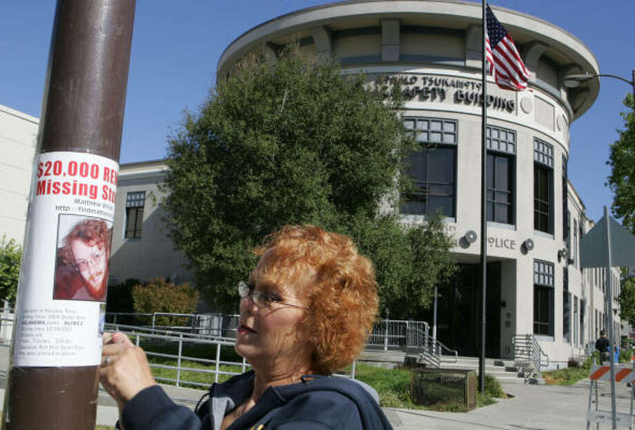 Cathy Wilson, the mother of missing Rice University student Matthew Wilson, hangs a missing person poster in front of the police station in Berkeley, Calif., on Aug. 1. Photo: Kat Wade, For The Chronicle