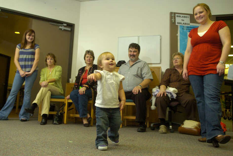 Morgan Stafford, 18 months, dances to the holiday music of Kevin Groover and Ivan Collins during the Christmas party and open house at the Baldwin Boettcher Branch Library in Spring on Dec. 22. Photo: Jerry Baker, For The Chronicle