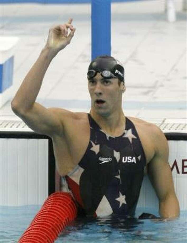 El estadounidense Michael Phelps festeja el martes su novena medalla de oro olímpica, la tercera que gana en los Juegos de Beijing, tras imponerse en la prueba de 200 metros estilo libre con récord mundial. Photo: Anja Niedringhaus, AP