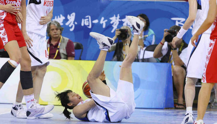 Korea's Choi Younah falls to the court after struggling for control of the ball with Russia. Photo: EDWARD A. ORNELAS, San Antonio Express-News
