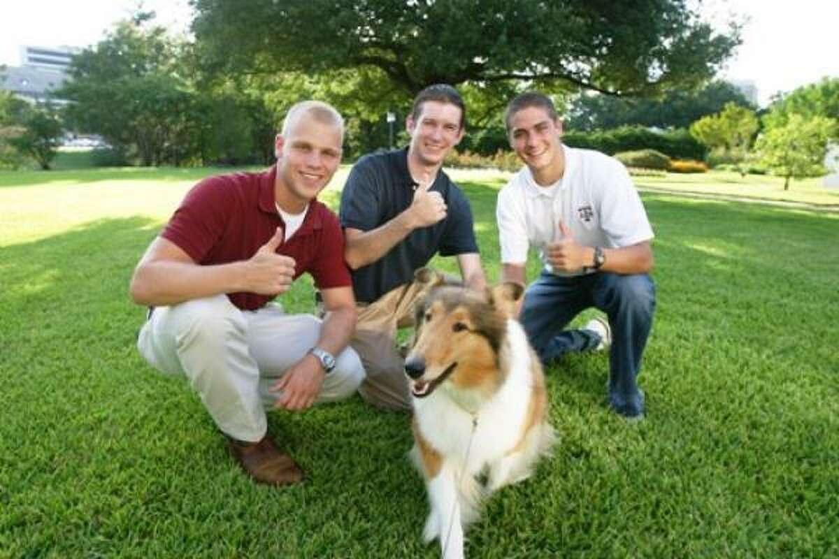 Reveille VIII poses with handler John Busch, left, Cody Vasut, speaker of the student senate, and Mark Gold, student body president.