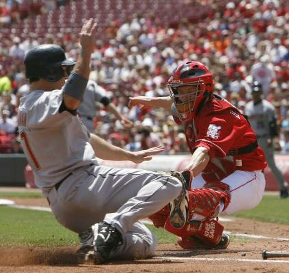 Lance Berkman, left, is tagged out at home plate by Reds catcher Ryan Hanigan after a Hunter Pence ground ball in the first inning. Photo: David Kohl, AP