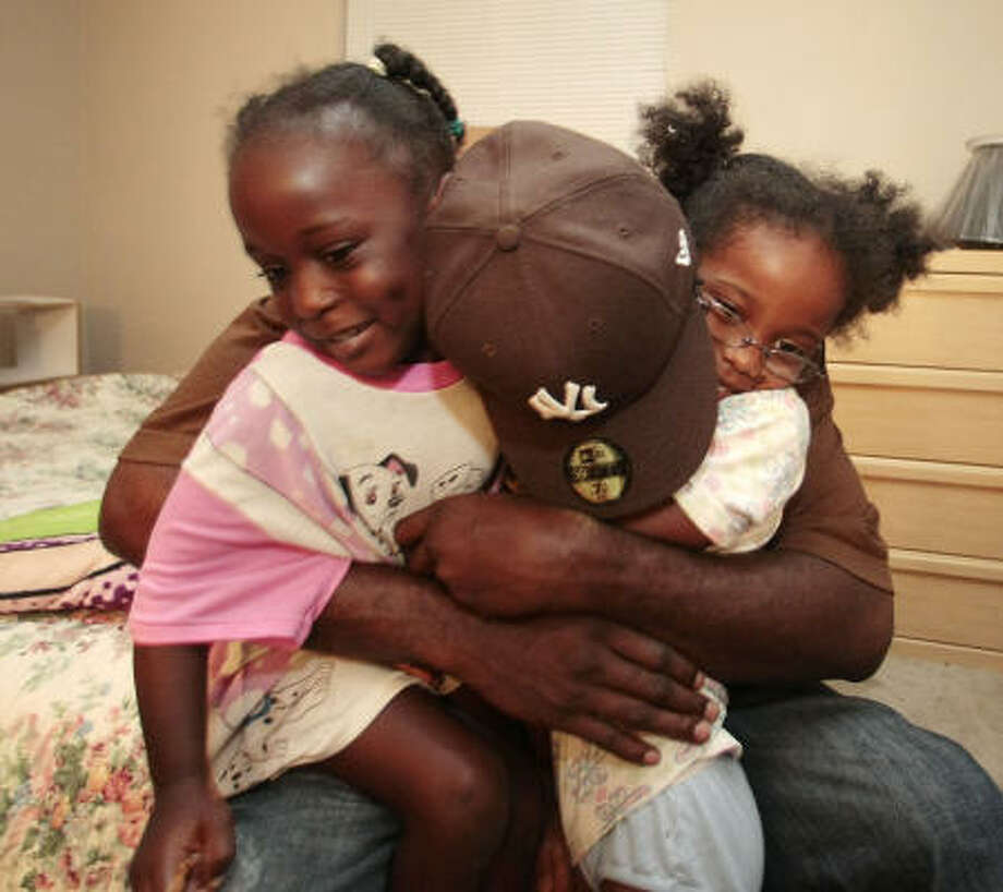 David Alfred hugs his daughters, Yasmine Alphonse, 4, and  Alaysa Alphonse, 6, on Friday Aug. 8, at their aunt's home in Houston. Photo: Billy Smith II, CHRONICLE