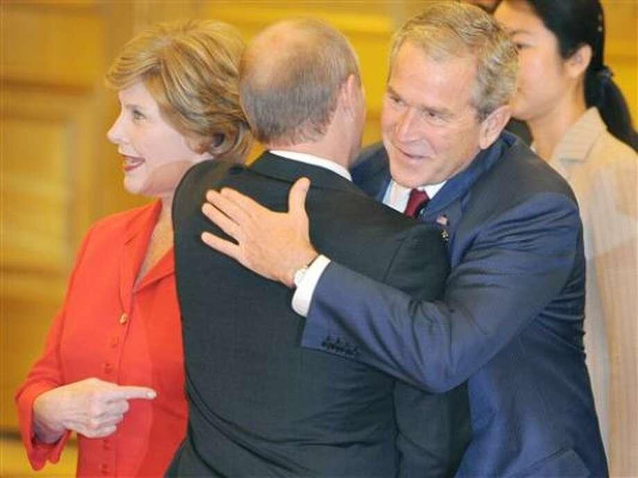 El presidente George Bush (centro, izq.) saluda al primer ministro ruso Vladimir Putin en el banquete de bienvenida en Beijing, China. Photo: Guang Niu, AP
