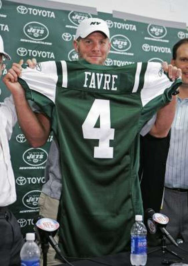 Brett Favre holds up his new New York Jets jersey at during a press conference Thursday at Cleveland Browns Stadium to introduce him as the newest Jet. Favre was traded from the Green Bay Packers to the Jets earlier in the day. Photo: Mark Duncan, AP