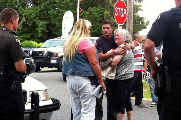 Joel James, center, comforts the mother of 22-year-old David Albrecht who was killed Wednesday in a confrontation with Shoreline police. Photo: Casey McNerthney/seattlepi.com