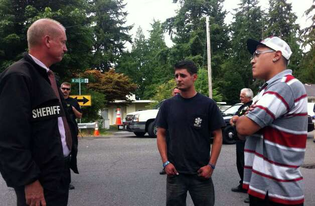 King County Sheriff's Sgt. John Urquhart talks to Joel James, center, and Edgar Sanchez near the property where their friend, David Albrecht, was fatally shot by Shoreline officers Aug. 10, 2011. Photo: Casey McNerthney/seattlepi.com