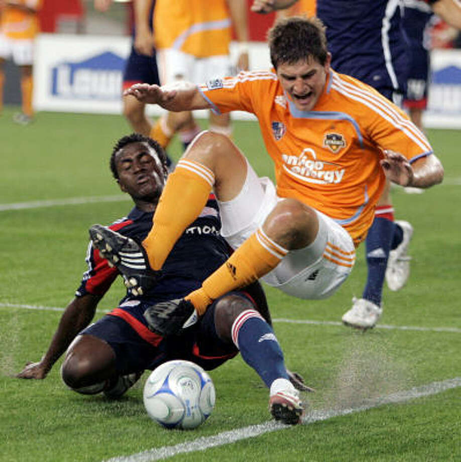 Houston Dynamo's Bobby Boswell, right, and New England Revolution's Kenny Mansally vie for the ball during the first half of the SuperLiga final soccer match. Photo: Michael Dwyer, AP
