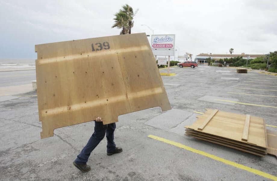 Hugo Portillo retira las planchas de madera que utilizó para proteger el hotel Guido's Seaside Inn, en la calle 37 y Seawalll Blvd. de Galveston, el martes 5 de agosto. Photo: Melissa Phillip, Houston Chronicle