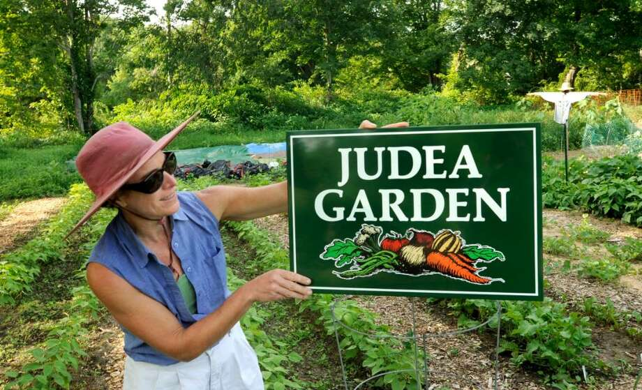 Denise Arturi, member of a ministry that grows produce which is donated to those who can't afford it, puts up a sign in the Washington garden they tend, on thursday. Photo: Michael Duffy / The News-Times