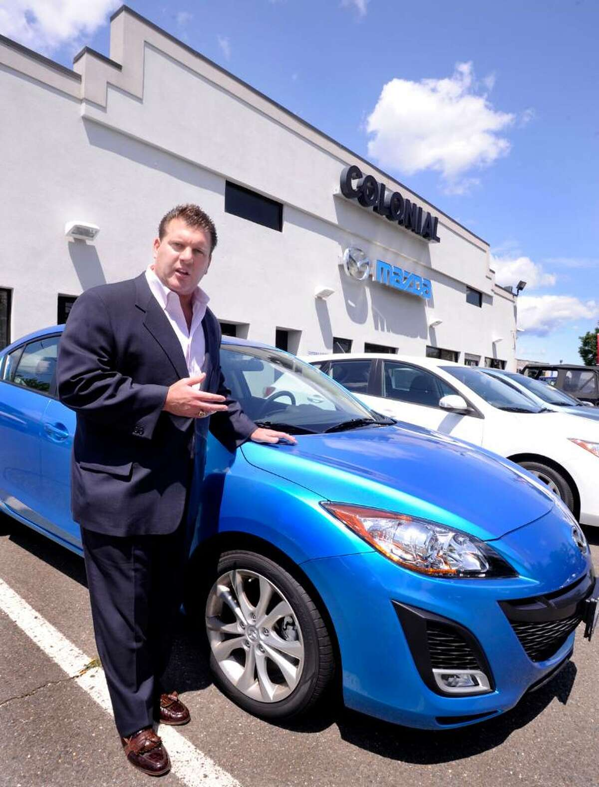 David Beylouni, president of Colonial Mazda in Danbury, talks about the 2010 Mazda 3, one of the fuel efficent cars that clunkers are being traded for, on friday.