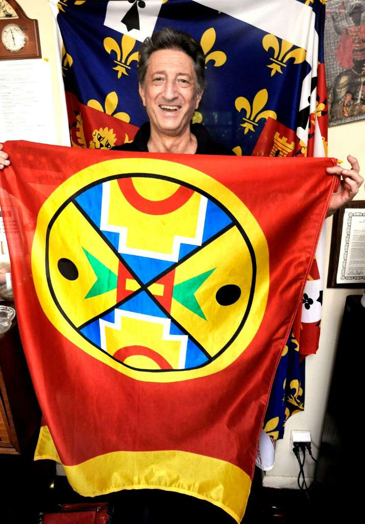 """Peter Orenski, aka """"the FlagDude"""", holds a flag of the Aroostook tribe of Maine in front of a flag of John of Gault, a historical flag of England, in his New Milford headquarters on friday."""