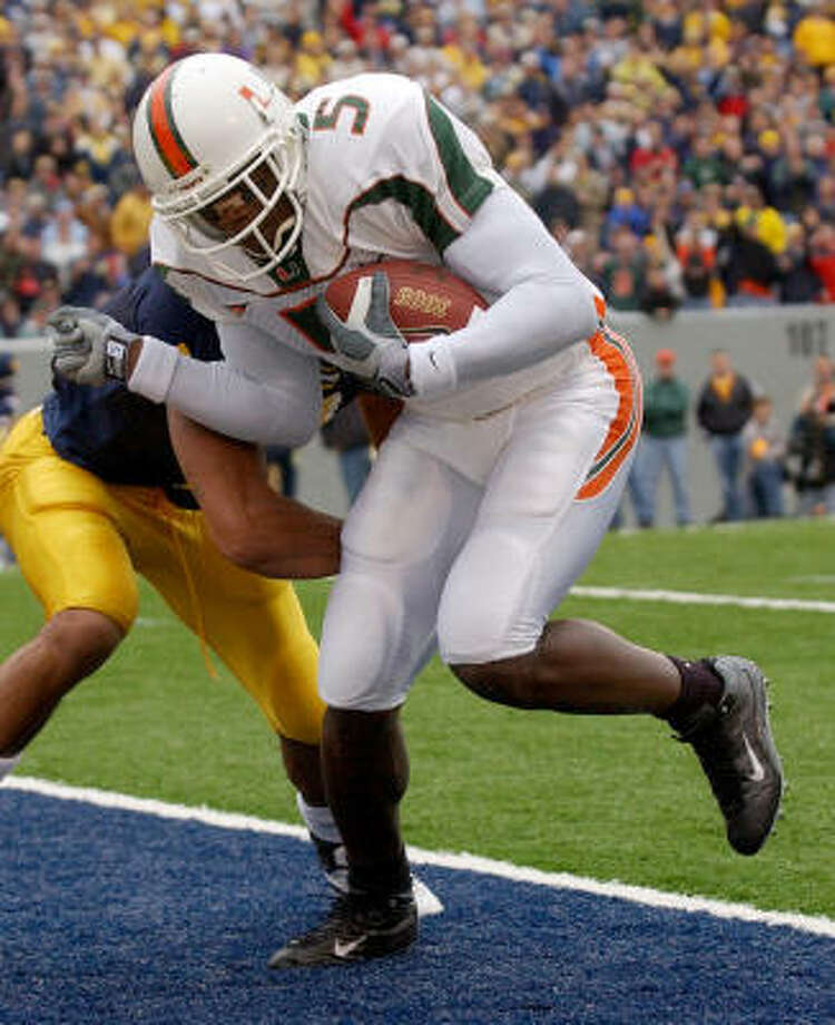 Andre Johnson wore the No. 5 jersey when he played for the University of Miami HURRICANES. In this photo, Johnson makes it past Angel Estrada (7) of the West Virginia University Mountaineers for an 11-yard touchdown reception to make the score 30-23. The Hurricanes defeated the Mountaineers 40-23 on October 26, 2002. Photo: Doug Pensinger, Getty Images