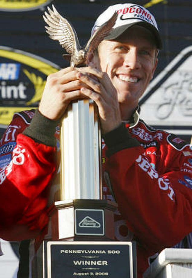 NASCAR driver Carl Edwards holds the trophy after winning the NASCAR Sprint Cup Series Pennsylvania 500 auto race. Photo: Nam Y. Huh, AP