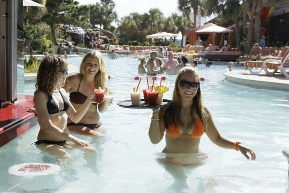 San Luis Resort employees Corinne Sheehan, left, and Tiffany Theobald, center, pose at swim-up bar with aqua server Tanya Al-Jazrawi, right,  at the H2O pool in Galveston. Photo: Melissa Phillip, Houston Chronicle