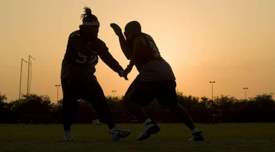 July 31:Texans defensive tackles Travis Johnson, left, and Amobi Okoye run pass rush drills as the sun sets on practice. Photo: Brett Coomer, Chronicle