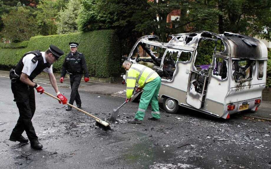 Merseyside Police officers help clean up a burnt out caravan in  the Toxteth area of Liverpool, England Wednesday Aug. 10, 2011 following  rioting in the area Tuesday night. Thousands of extra police officers flooded into London  in a bid to end Britain's worst rioting in a generation. An eerie calm prevailed in the capital, but unrest spread across England on a fourth night of violence driven by diverse and brazen crowds of young people (AP Photo/Peter Byrne/PA) UNITED KINGDOM OUT NO SALES NO ARCHIVE Photo: Peter Byrne, SUB / PA