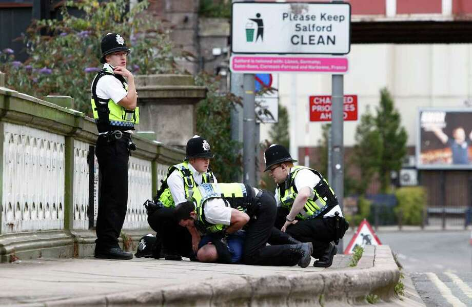Police detain a person during civil disturbances in Manchester, England, Tuesday Aug. 9 2011.  Three nights of looting and burning by crowds of young people appears to have spread from the capital to other locations in Britain. (AP Photo/Jon Super). Photo: JON SUPER / AP
