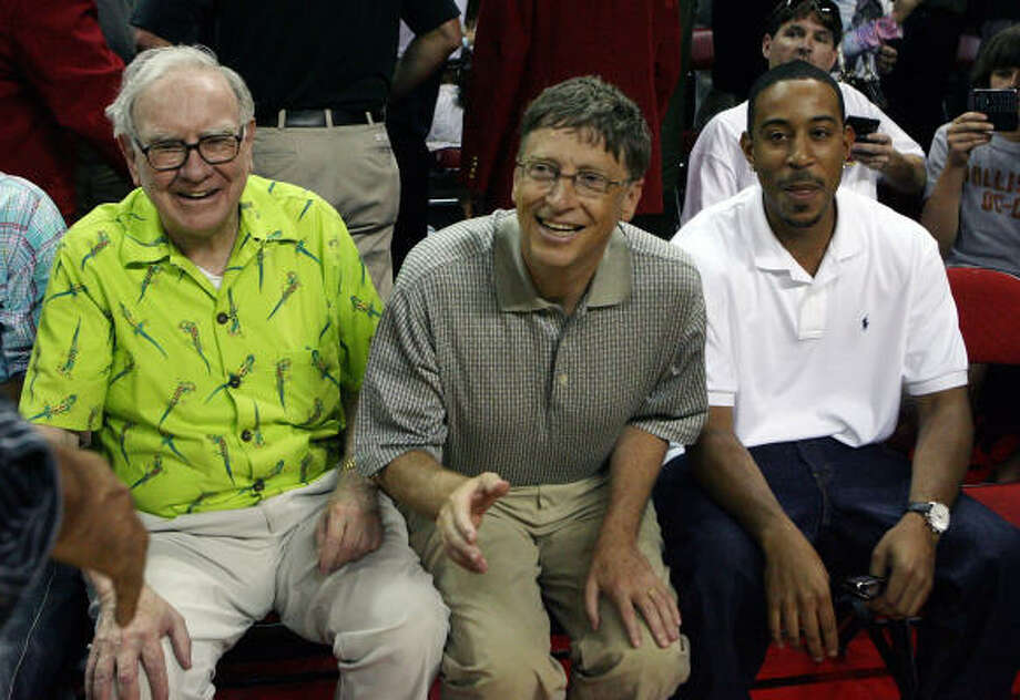 (L-R) Warren Buffett, Bill Gates and rapper Ludacris enjoy the exhibition contest from their courtside seats. Photo: Ethan Miller, Getty Images