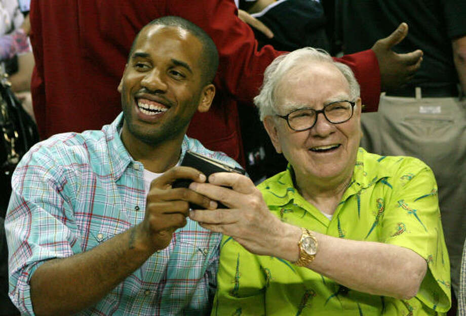 Maverick Carter (L) and Warren Buffett joke around courtside with Buffett's wallet. Photo: Ethan Miller, Getty Images