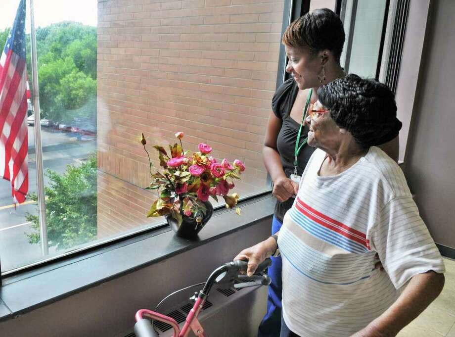 Health aide Letricia Smith, left, and her patient Evelyn Thompson stop to look out of a window during an exercise walk outside Thompson's Townsend Park homes apartment in Albany on Wednesday Aug. 10, 2011.  (John Carl D'Annibale / Times Union) Photo: John Carl D'Annibale / 00014225A