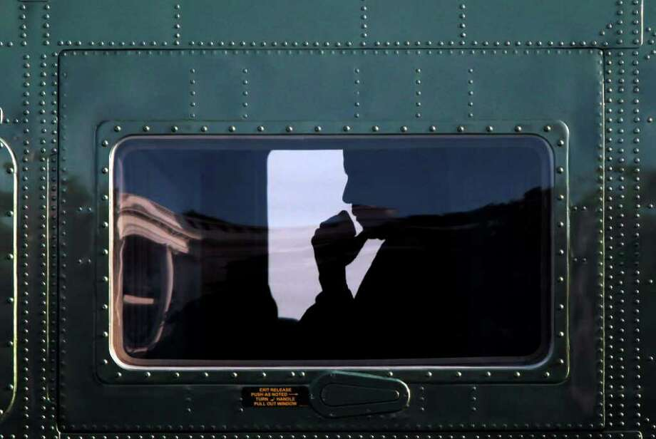President Barack Obama is seen silhouetted inside Marine One helicopter during his arrival on the South Lawn of the White House, Tuesday, Aug. 9, 2011 in Washington. Obama made an unannounced trip to Dover Air Force Base in Dover, Delaware, to pay tribute to the 30 U.S. troops killed over the weekend in Afghanistan. (AP Photo/Pablo Martinez Monsivais) Photo: Pablo Martinez Monsivais