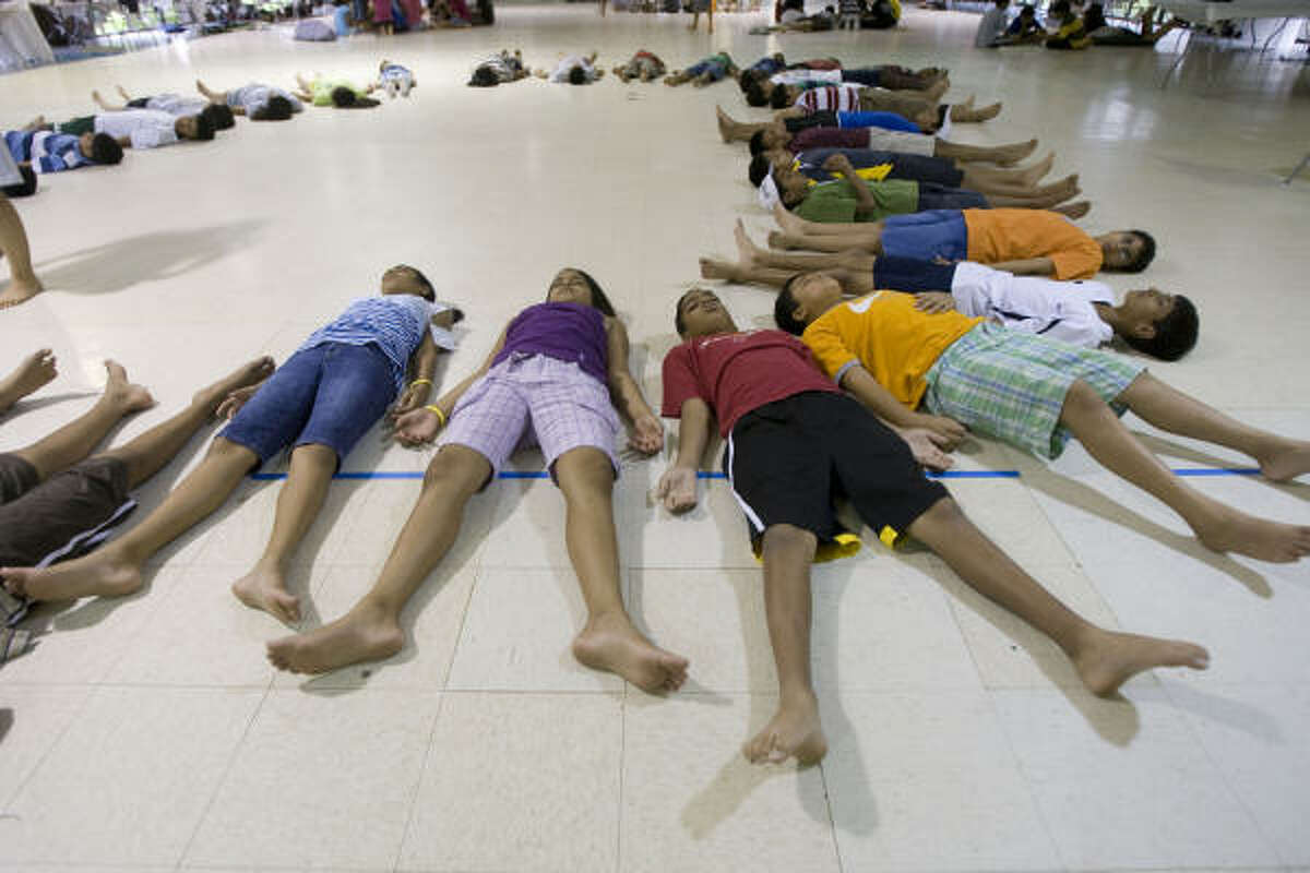 Camp attendees lay on the floor during a yoga exercise at the Hindu Heritage Youth Camp at Gordon Ranch on Thursday, July 24, in Richmond.