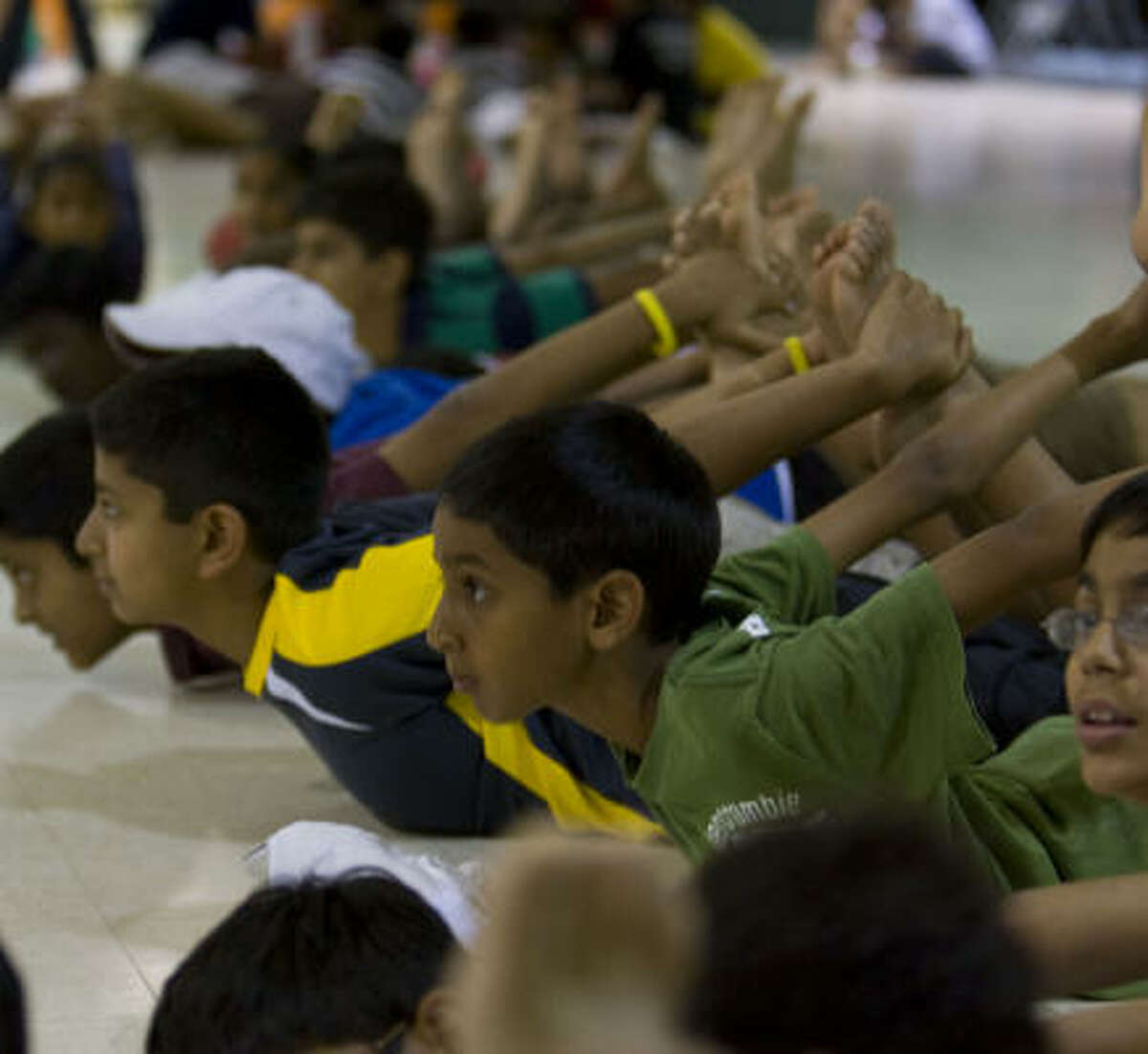 Camp attendees hold a yoga position during the Hindu Heritage Youth Camp at Camp Gordon on Thursday, July 24, in Richmond.