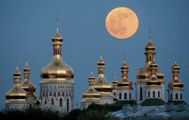 In this 2004 file photo a full moon rises in during a lunar eclipse above the golden domes of the Orthodox Monastery of Caves in Kiev, Ukraine. Celebrations marking the 1020th anniversary of this region's conversion to Christianity may turn into a fierce political battle with Ukrainian officials are determined to use the events to lobby for autonomy for the local church from Russia, while the dominant Moscow Patriarchate will fi