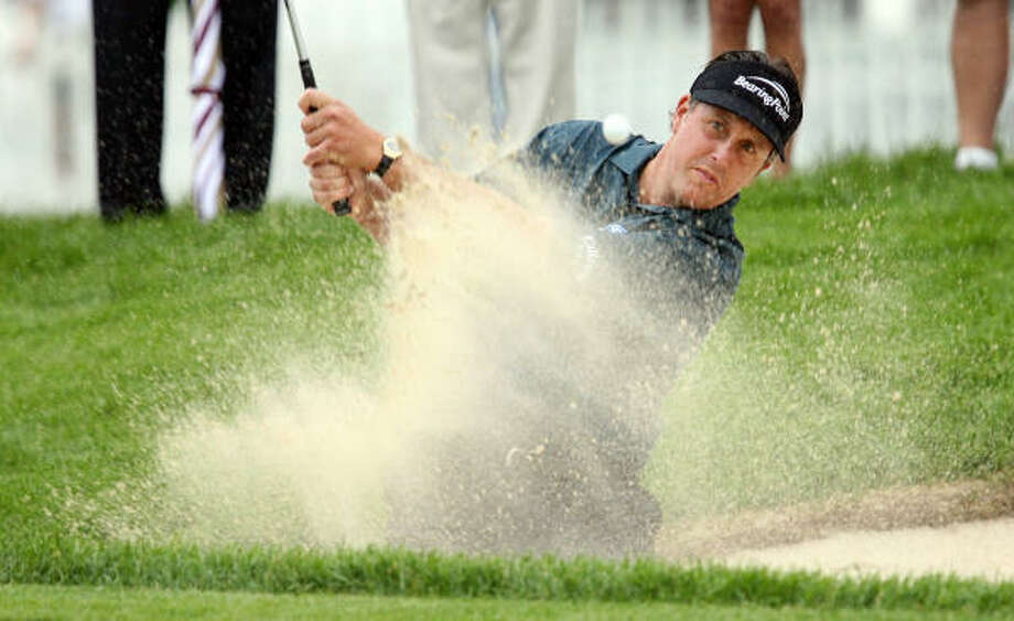 Phil Mickelson found the bunker on No. 12 but is stationed near the top of the leaderboard at Winged Foot. Photo: TIM SLOAN, AFP/Getty Images