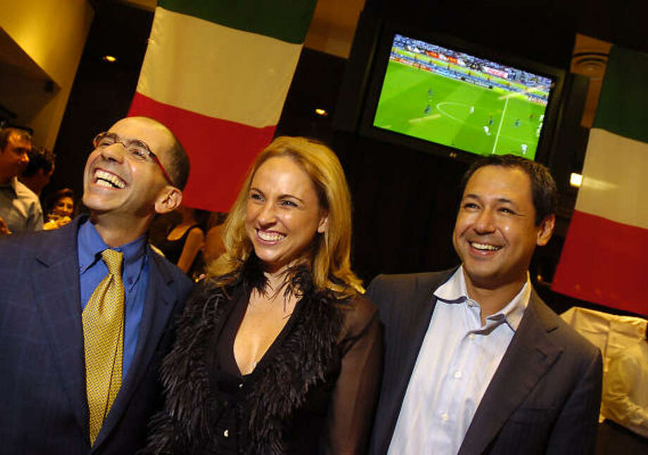 Italian Consul General Cristiano Maggipinto, left, Patricia Sturion and Hector Villarreal welcome guests to the World Cup celebration at Lucho. Photo: Dave Rossman, For The Chronicle