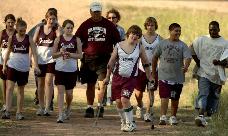 Franklin Middle School seventh-grader Daniel Reed works his way to the finish line on crutches during a cross country meet as his coach, Jerry Johnson, and teammates offer encouragement. Photo: TOMMY METTHE, Abilene Reporter-News