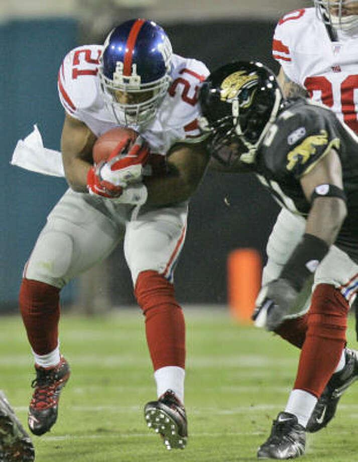 Giants RB Tiki Barber, left, runs for yardage against the Jaguars. Photo: PHIL COALE, AP