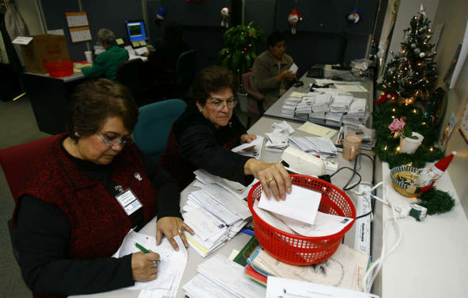 Lourdes Reyes, left, and Rosa Cortez, both of Houston, are part of the team that reads and sorts letters from parents to Goodfellows. Each letter is read individually, then coded by the children's ages. Photo: Nick De La Torre, CHRONICLE